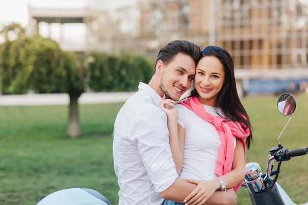 Spettacolare donna in bracciale d'argento che accarezza dolcemente il marito, posando con lui in piazza Foto Gratuite