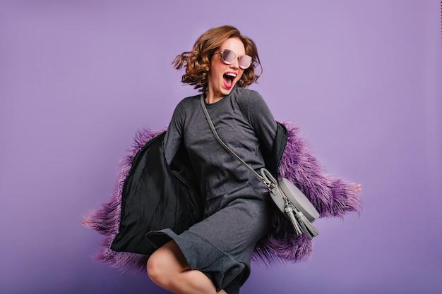 Эффектная женщина с возбужденным выражением лица прыгает на фиолетовом фоне и поет Бесплатные Фотографии