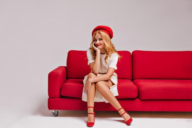 Эффектная блондинка у красного дивана