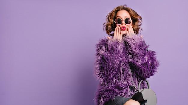 Spettacolare giovane donna con trucco alla moda in posa con l'espressione del viso sorpreso su sfondo viola brillante Foto Gratuite