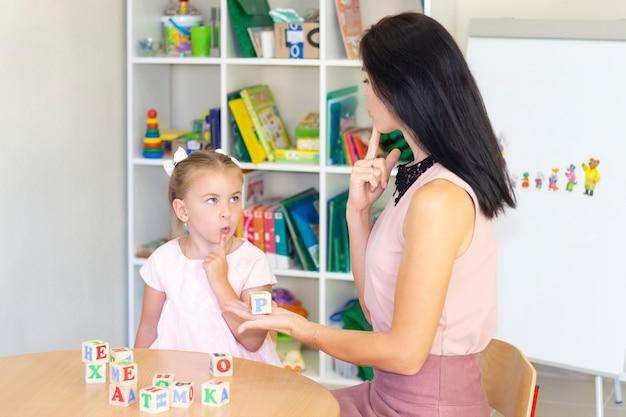 Speech therapist teaches the girl to speak Premium Photo