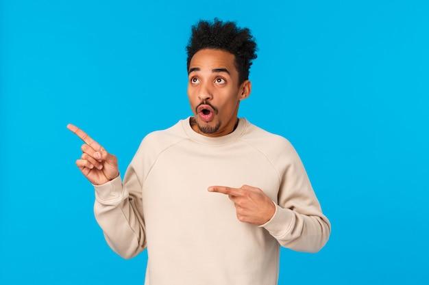 Безмолвный и впечатленный, пораженный привлекательный афро-американский парень видит именно то, что ему нужно Premium Фотографии