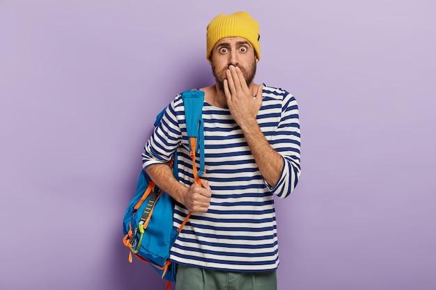 無言の感情的なバックパッカーは口に手のひらを保持し、目を信じることができず、アクティブなライフスタイルを持っています 無料写真