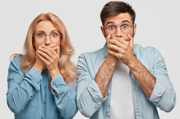 言葉のない素敵なブロンドの女性とハンサムな男が口を覆い、何かひどいものを見るのを恐れています 無料写真