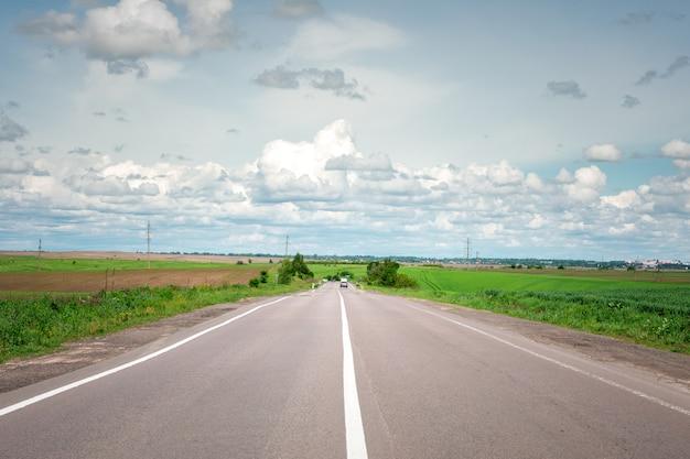 Speed highway through the field. asphalt-paved road Premium Photo