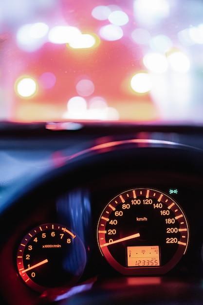 ぼかしボケ信号と夜の街で近代的な車車ドライブ旅行道路旅行のスピードメーター Premium写真