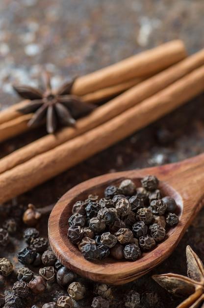 スパイスとハーブ。食品と料理の食材。テクスチャード加工の表面にシナモンスティック、アニススター、ブラックペッパーコーン、カルダモン。 Premium写真