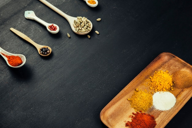 Spices composition with spoons and board Free Photo