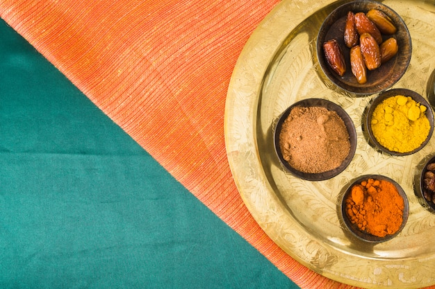 Spices and dry fruits on tray on textile Free Photo