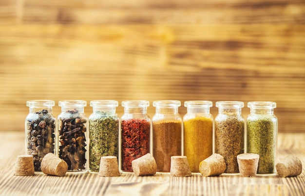 Spices in jars on wooden background. selective focus. Premium Photo