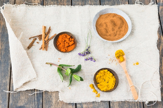 Spices near cinnamon and plant twig on textile on table Free Photo