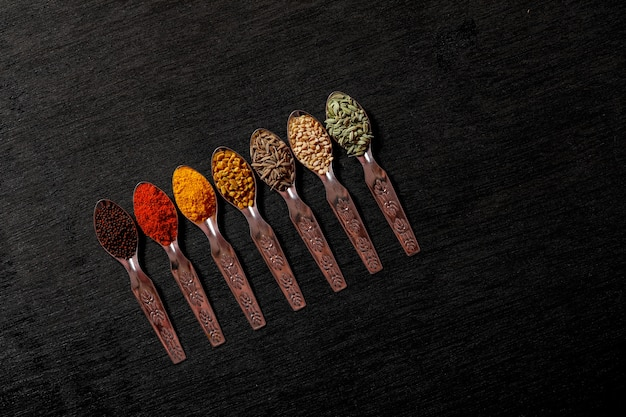 Spices in spoons on black background Premium Photo