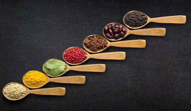 Spices in spoons over black table background. top view of season Premium Photo