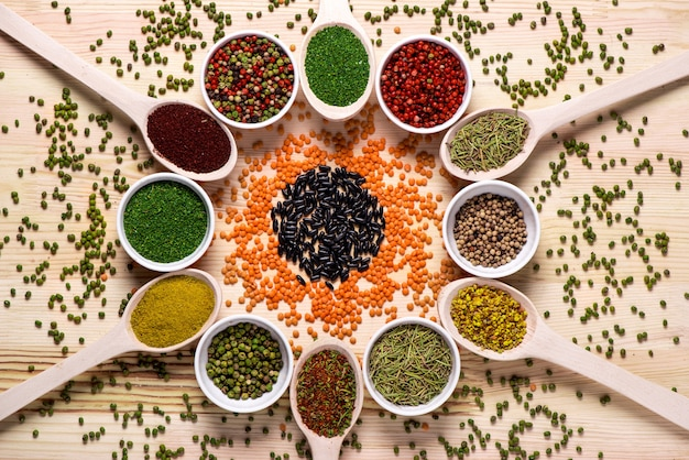 Spices in spoons on wooden table Free Photo