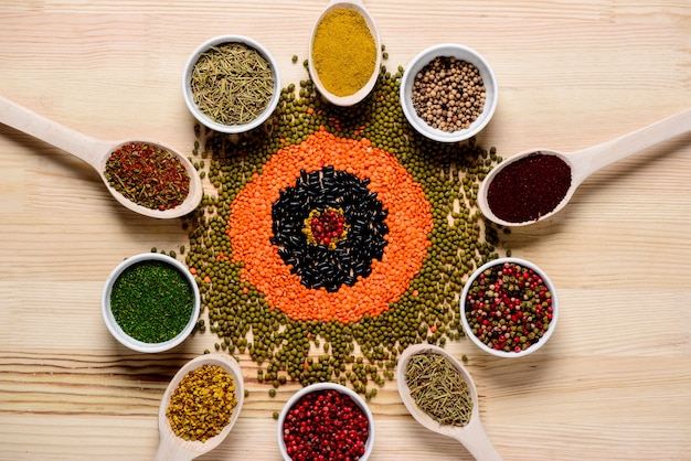 Spices in spoons and on wooden table Free Photo