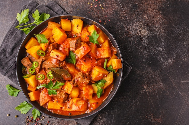 Spicy beef stewed with potatoes in tomato sauce in black plate. meat traditional goulash. Premium Photo