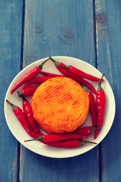 Spicy cheese with red pepper on white plate on blue wooden surface Premium Photo