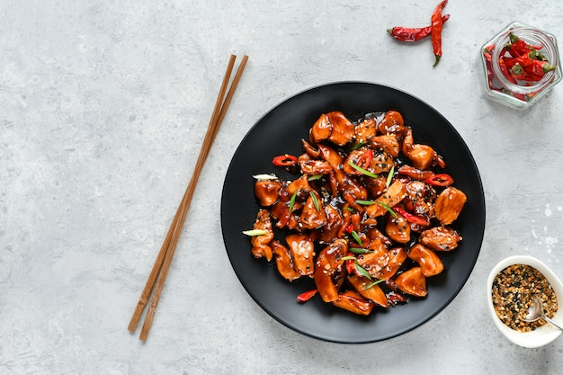 Spicy chicken in sweet and sour sauce with chili pepper. Premium Photo