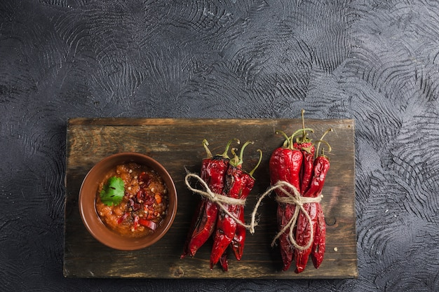 Spicy chili on a dark background in ceramic plates on a wooden board Premium Photo