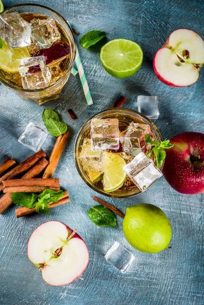 スパイシーなシナモンアップルアイスティーまたはレモネードカクテル、夏の飲み物、青いテーブル Premium写真