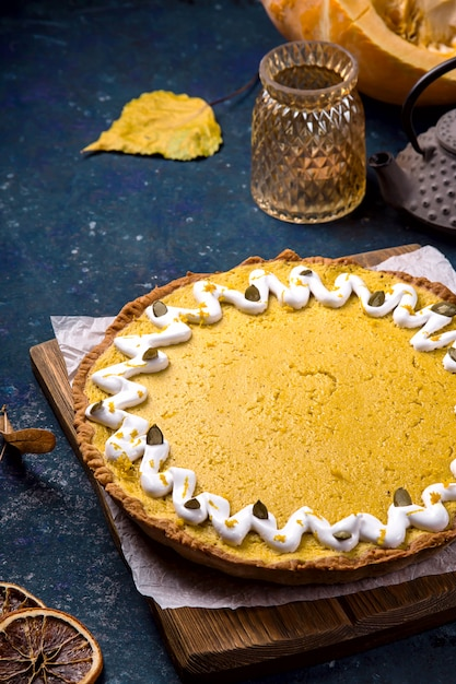 Spicy delicious round pumpkin pie decorated with white cream and pumpkin seeds Premium Photo