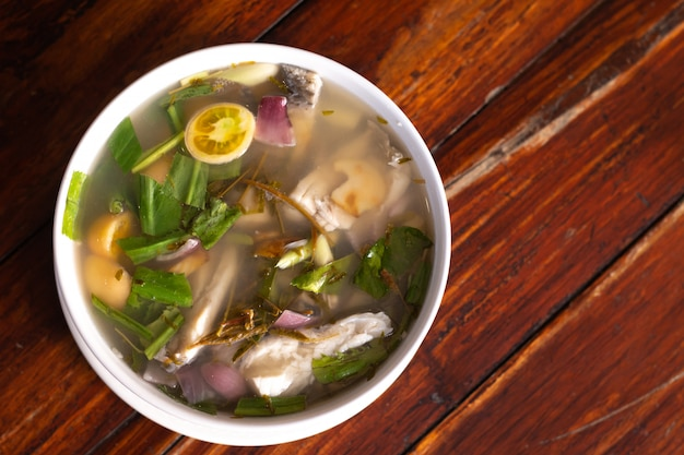 Spicy fish soup flavored with lemongrass and lime served on wooden table Premium Photo