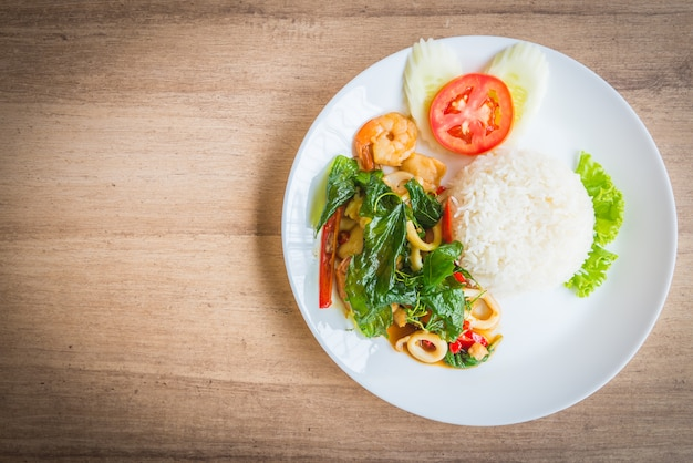 Spicy fried basil leaf with seafood and rice Free Photo