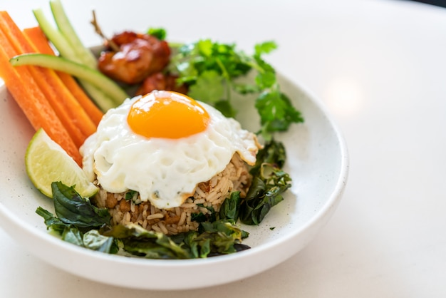 Spicy fried rice with fried egg and vegetable Premium Photo