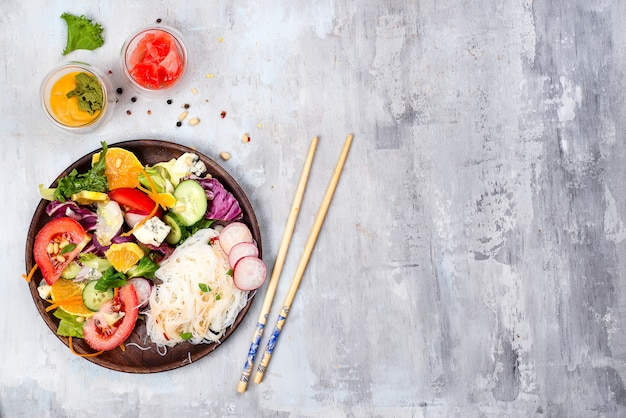 Spicy glass rice noodles and vegetables salad on stone background Premium Photo