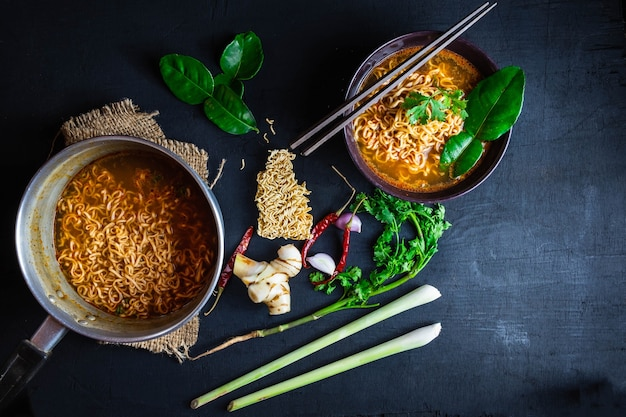 Spicy instant noodles soup and vegetables on a black background. Premium Photo