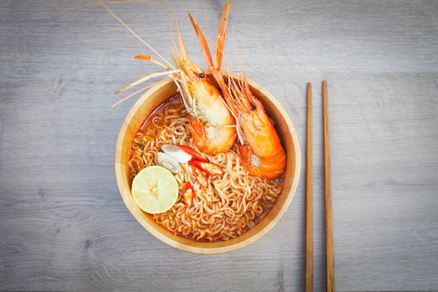 Spicy instant noodles soup with shrimp in wooden bowl on wood background Premium Photo