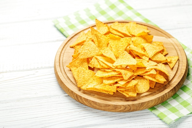 Spicy mexican nachos chips on a wooden tray. Premium Photo
