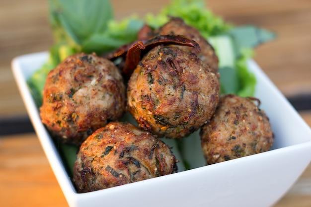 テーブルの上の白い皿にサラダとスパイシーミンチ豚ボール。タイ料理(larb moo tod) Premium写真