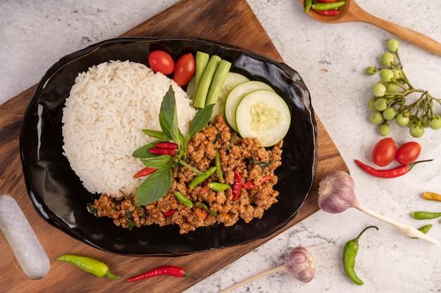 검은 접시에 매운 다진 돼지 고기와 쌀. 무료 사진