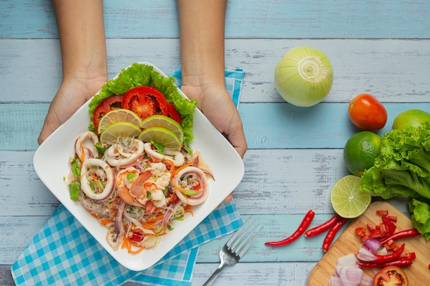 Spicy mixed seafood salad with thai food ingredients. Free Photo