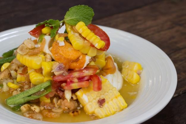 Spicy papaya salad with corn, salted eggs Premium Photo