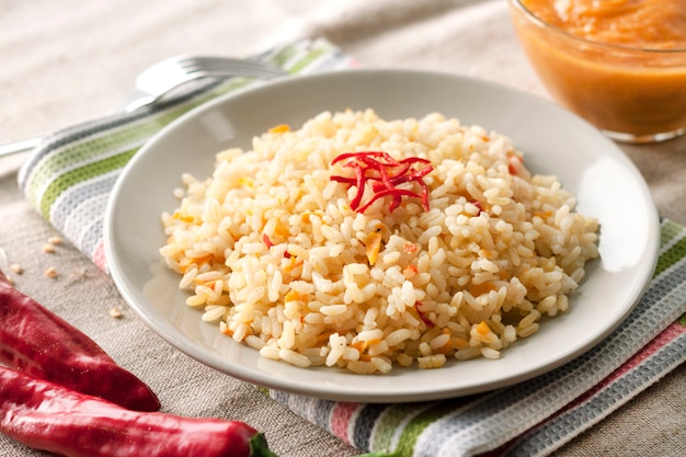 Острый пропаренный рис с морковью, желтыми цукини и перцем чили на серой тарелке Premium Фотографии