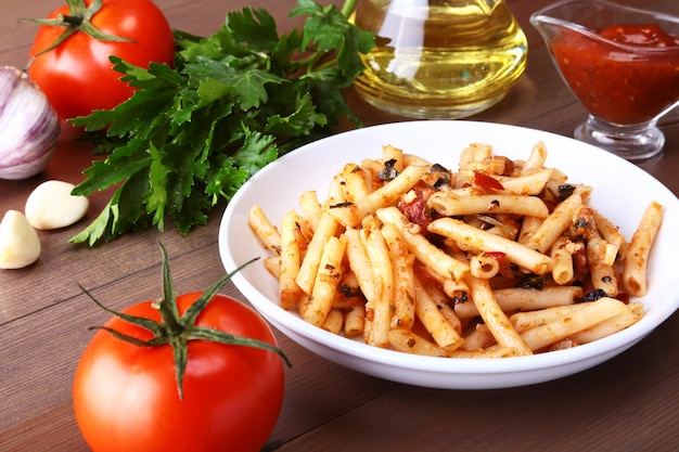 Spicy pasta penne bolognese with vegetables, chili and cheese in tomato sauce. Premium Photo