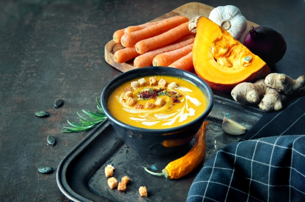 Spicy pumpkin and carrot soup with ginger, garlic, red onion and chili on dark surface Premium Photo