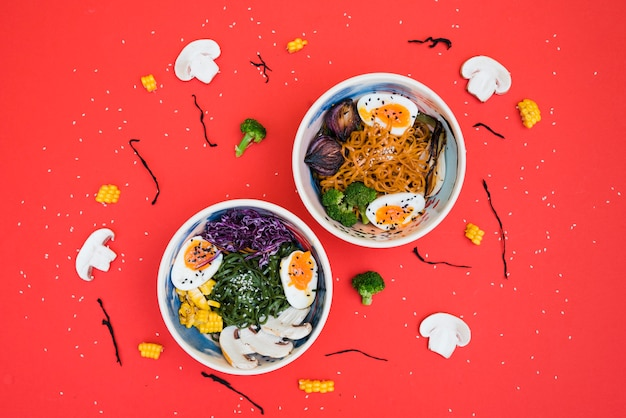 Spicy ramen bowls with noodles; boiled egg and vegetables served with seaweed salad on red backdrop Free Photo