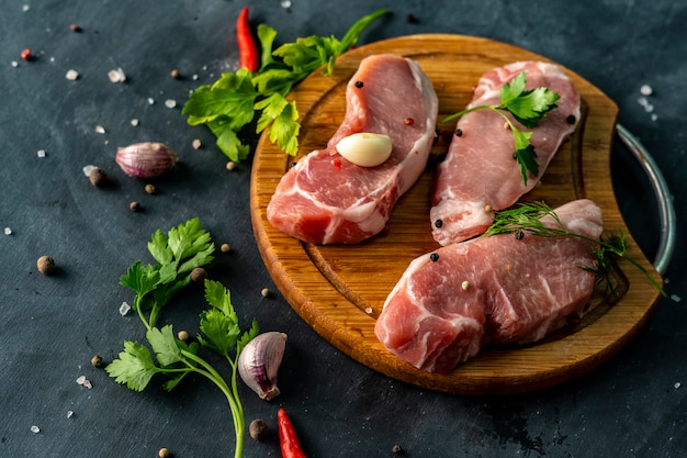 Spicy raw meat on a wooden slicing or cutting board, put a salt on an uncooked meats Premium Photo