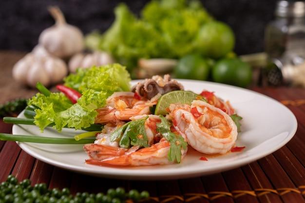 レモンコリアンダーとレタスを添えた白皿のスパイシーなイカとエビのサラダ 無料写真