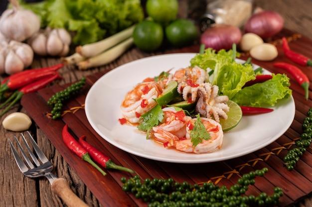 Острый салат из кальмаров и креветок в белом блюде с лимонной кинзой и листьями салата Бесплатные Фотографии