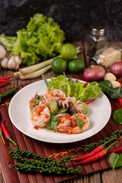 Insalata piccante di calamari e gamberetti in un piatto bianco con limone, coriandolo e lattuga Foto Gratuite