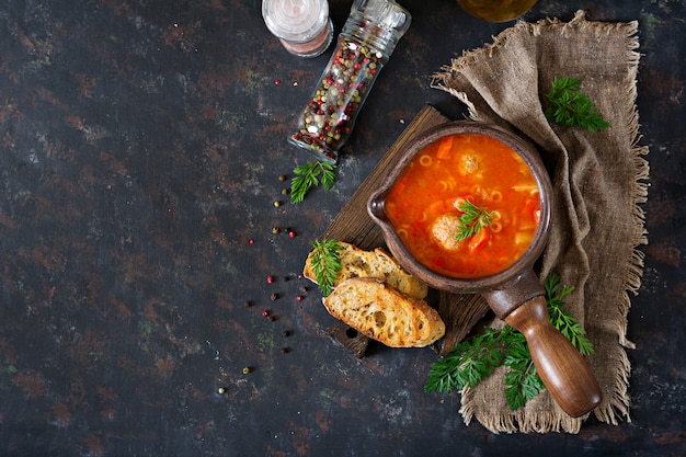 Spicy tomato soup with meatballs, pasta and vegetables.  healthy dinner. top view Free Photo