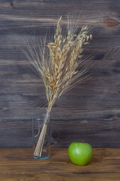 Spikes of wheat and barley in a vase on the background of wooden boards. Premium Photo