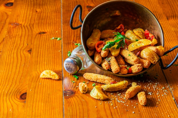 Spilled fried potato wedges from the copper utensil Free Photo