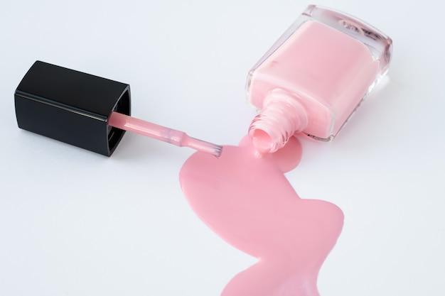 Пролитый лак для ногтей в стеклянной бутылке и кисти на белом фоне, розовая эмаль. Premium Фотографии
