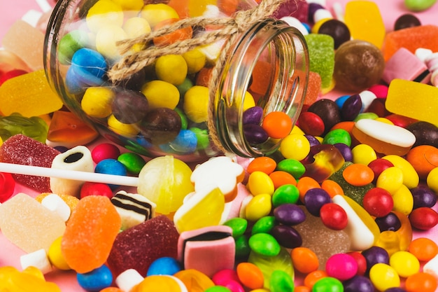 Spilled out colorful candies from glass jar Free Photo