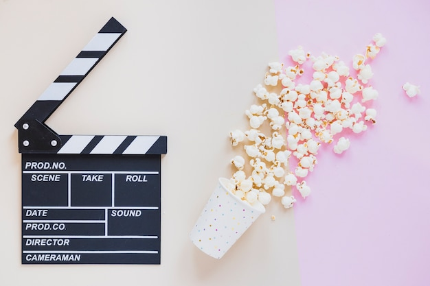 Spilled popcorn and clapperboard Free Photo